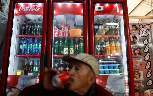 Un señor bebe refresco dentro de una tienda informal.